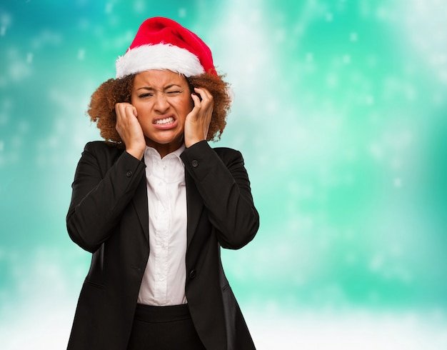 Young business black woman wearing a chirstmas santa hat covering ears with hands