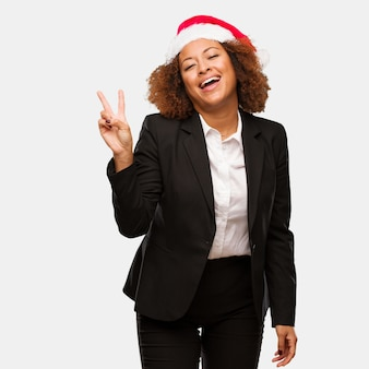 Young business black woman wearing a chirstmas santa hat doing a gesture of victory