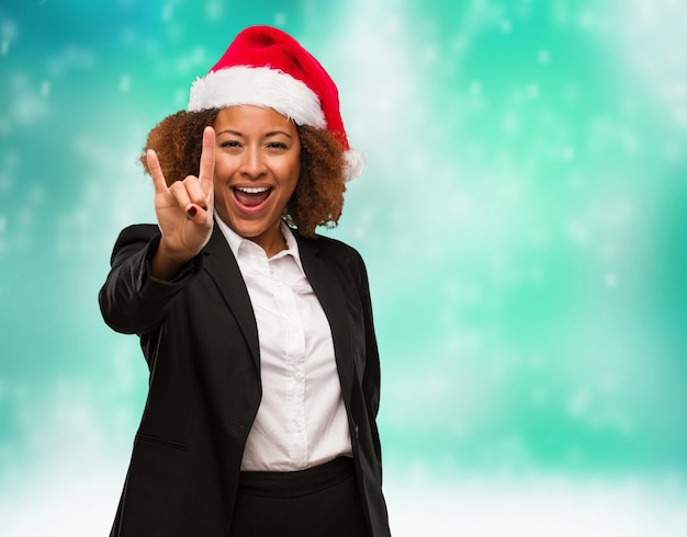 Young business black woman wearing a chirstmas santa hat doing a rock gesture