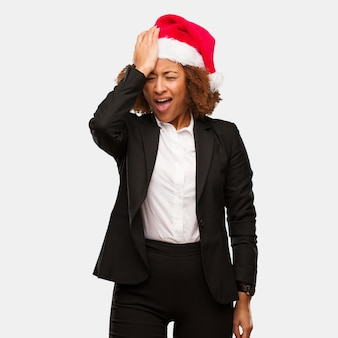 Young business black woman wearing a chirstmas santa hat forgetful, realize something