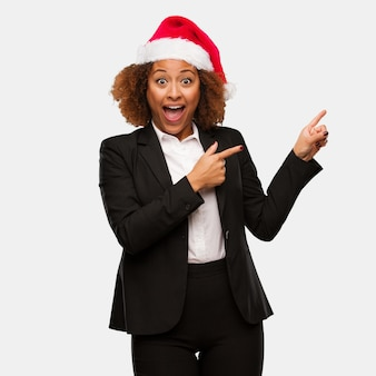 Young business black woman wearing a chirstmas santa hat holding something with hand