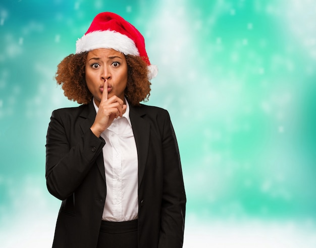 Young business black woman wearing a chirstmas santa hat keeping a secret or asking for silence