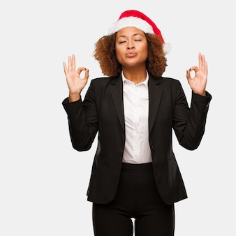 Young business black woman wearing a chirstmas santa hat performing yoga