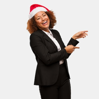 Young business black woman wearing a chirstmas santa hat pointing to the side with finger
