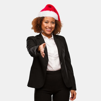 Young business black woman wearing a chirstmas santa hat reaching out to greet someone