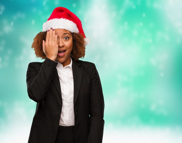 Young business black woman wearing a chirstmas santa hat shouting happy and covering face with hand