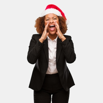 Young business black woman wearing a chirstmas santa hat shouting something happy to the front