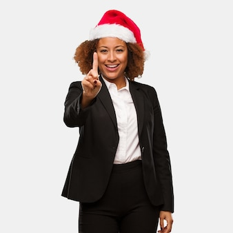 Young business black woman wearing a chirstmas santa hat showing number one