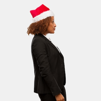 Young business black woman wearing a chirstmas santa hat on the side looking to front