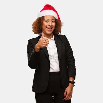 Young business black woman wearing a chirstmas santa hat smiling and raising thumb up
