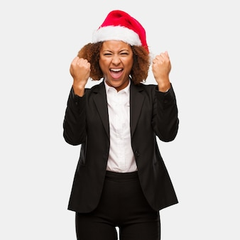 Young business black woman wearing a chirstmas santa hat surprised and shocked