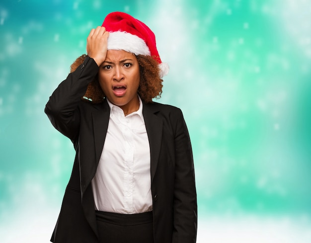 Young business black woman wearing a chirstmas santa hat tired and very sleepy