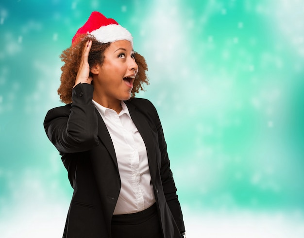 Young business black woman wearing a chirstmas santa hat try to listening a gossip