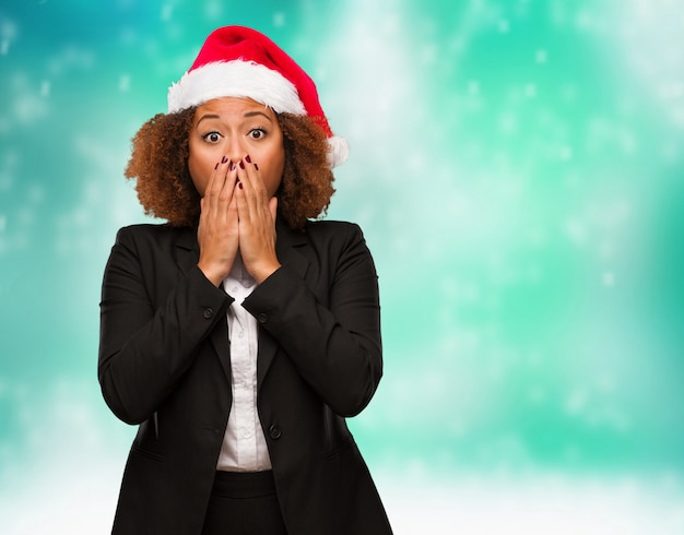 Young business black woman wearing a chirstmas santa hat very scared and afraid hidden