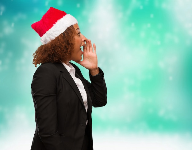 Young business black woman wearing a chirstmas santa hat whispering gossip undertone