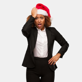 Young business black woman wearing a chirstmas santa hat worried and overwhelmed
