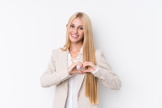 白の笑顔と手でハートの形を示す若いビジネスブロンドの女性。