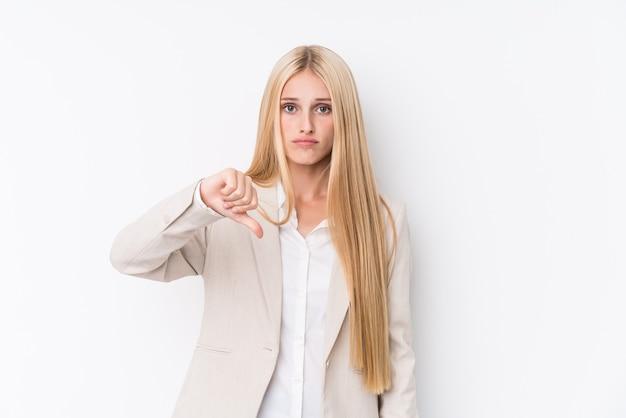 Молодой бизнес блондинка женщина на белой стене, показывая неприязнь жест, пальцы вниз. концепция несогласия.