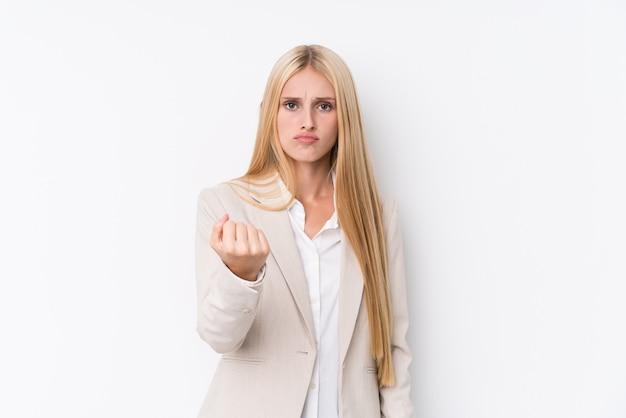 Женщина молодого дела белокурая на белой стене показывая кулак с агрессивным выражением лица.