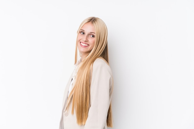 Young business blonde woman on white background looks aside smiling, cheerful and pleasant.