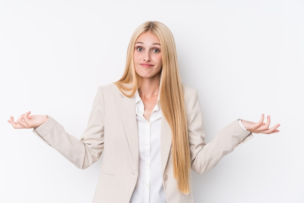 Young business blonde woman on white wall doubting and shrugging shoulders in questioning gesture.
