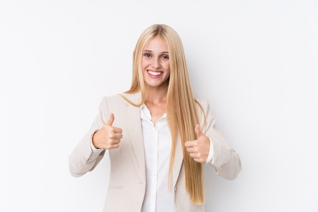 Young business blonde woman on white wall raising both thumbs up, smiling and confident.