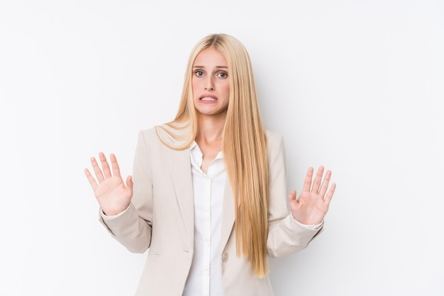 Young business blonde woman on white wall rejecting someone showing a gesture of disgust.