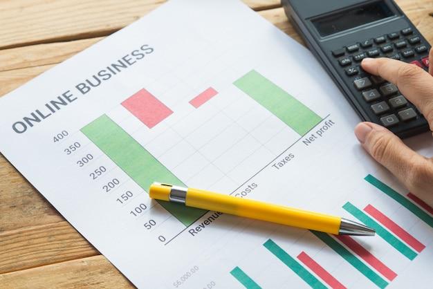 Молодой бизнес занят работой, предприниматель анализирует финансовую информацию в виде графиков