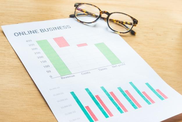 グラフィックとして財務情報を分析する起業家で忙しい若いビジネス