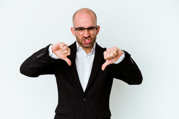 Young business caucasian bald man on blue showing thumb down and expressing dislike.