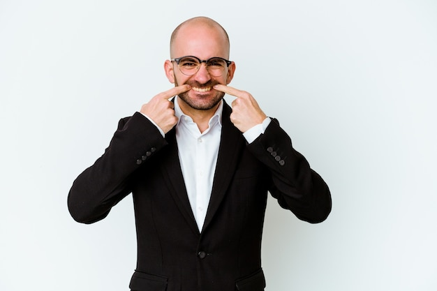 Young business caucasian bald man on blue smiles, pointing fingers at mouth.