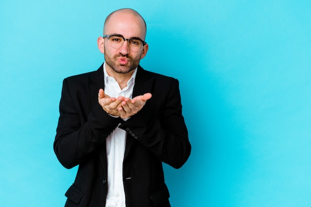 Young business caucasian bald man isolated on blue background folding lips and holding palms to send air kiss.