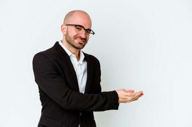 Young business caucasian bald man isolated on blue background holding a copy space on a palm.