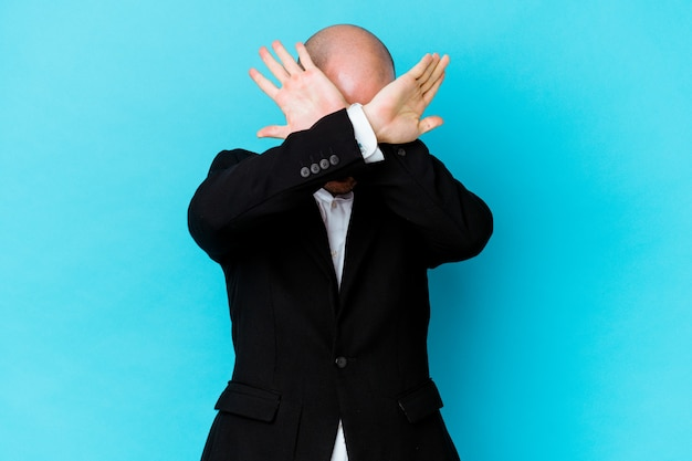 Young business caucasian bald man isolated on blue background keeping two arms crossed, denial concept.