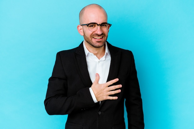 Young business caucasian bald man isolated on blue background laughs out loudly keeping hand on chest.