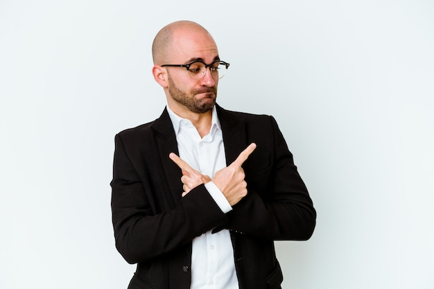 Young business caucasian bald man isolated on blue background points sideways, is trying to choose between two options.