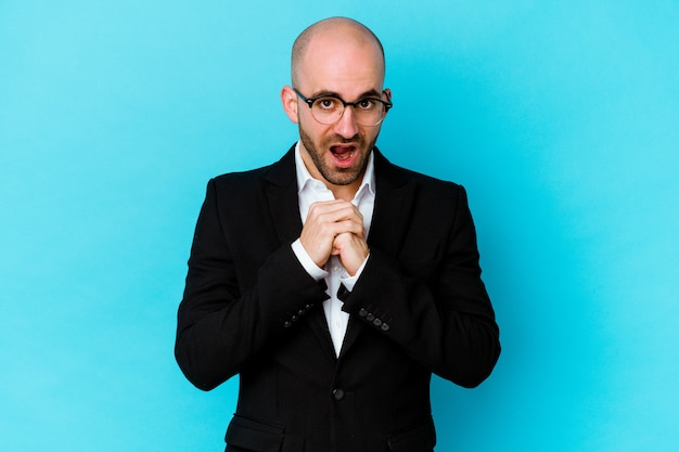 Young business caucasian bald man isolated on blue background praying for luck, amazed and opening mouth looking to front.