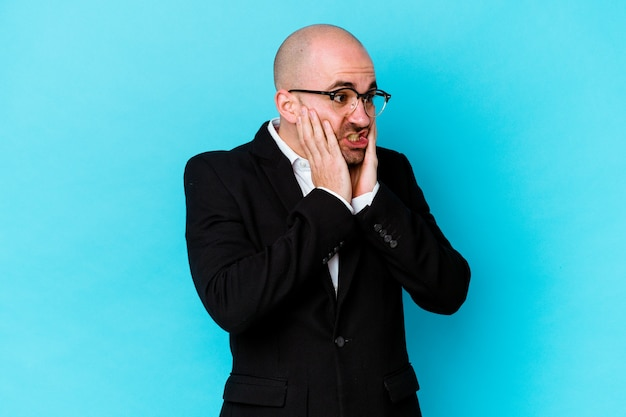Young business caucasian bald man isolated on blue background scared and afraid.