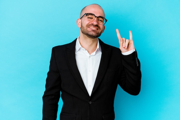 Young business caucasian bald man isolated on blue background showing a horns gesture as a revolution concept.