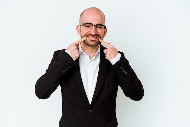 Young business caucasian bald man isolated on blue background smiles, pointing fingers at mouth.