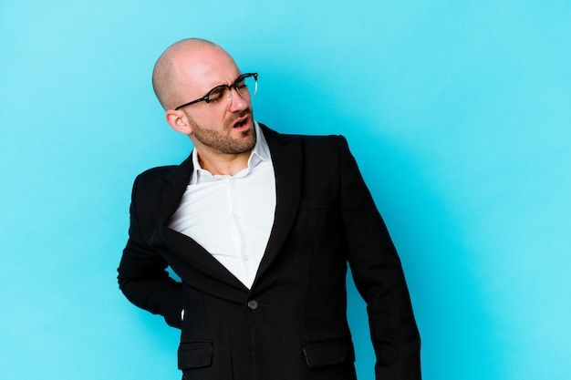 Young business caucasian bald man isolated on blue background suffering a back pain.