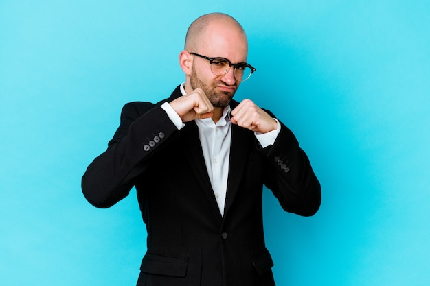 Young business caucasian bald man isolated on blue background throwing a punch, anger, fighting due to an argument, boxing.