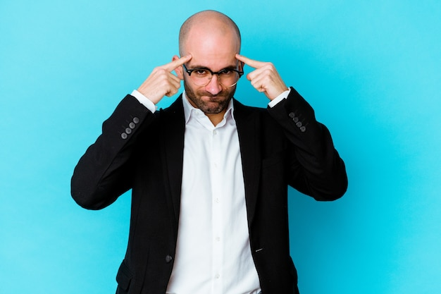 Young business caucasian bald man isolated on blue wall focused on a task, keeping forefingers pointing head