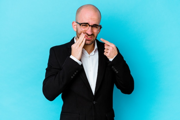 Young business caucasian bald man isolated on blue wall having a strong teeth pain, molar ache.