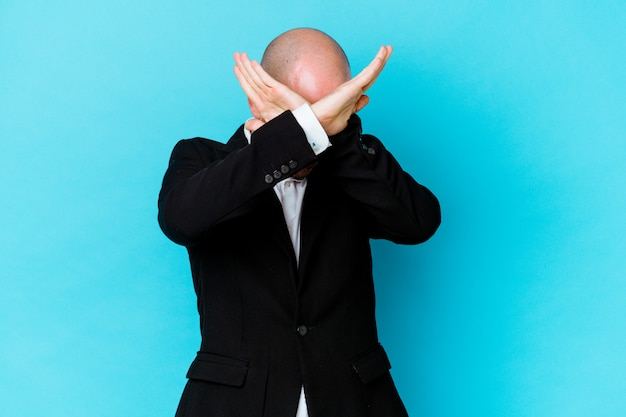 Young business caucasian bald man isolated on blue wall keeping two arms crossed, denial concept.