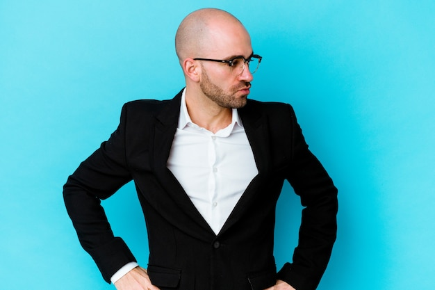 Young business caucasian bald man isolated on blue wall looks aside smiling, cheerful and pleasant.