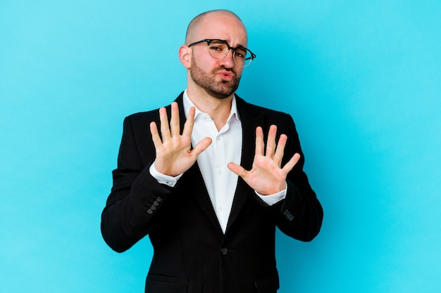 Young business caucasian bald man isolated on blue wall rejecting someone showing a gesture of disgust.