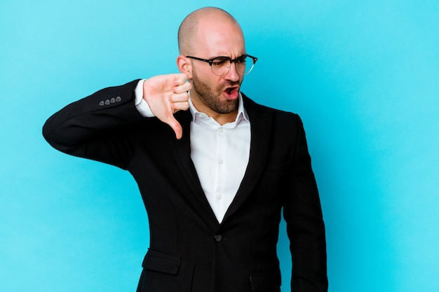 Young business caucasian bald man isolated on blue wall showing thumb down and expressing dislike.