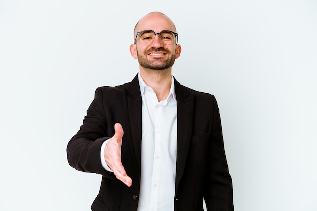 Young business caucasian bald man isolated on blue wall stretching hand in greeting gesture.