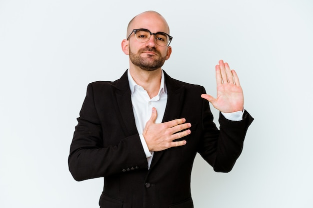 Young business caucasian bald man isolated on blue wall taking an oath, putting hand on chest.